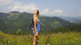 Young beautiful blonde girl posing in the mountains on a background of clouds.  stock video