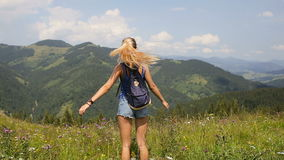 Young beautiful blonde girl posing in the mountains. Young beautiful blonde girl posing in the mountains on a background of clouds stock footage