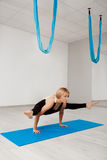 Young beautiful blonde girl practicing yoga in gym. Royalty Free Stock Image