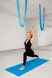 Young beautiful blonde girl practicing yoga in gym. Stock Photos
