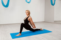 Young beautiful blonde girl practicing yoga in gym. Stock Images