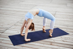 Young beautiful blonde girl practicing yoga outside. Stock Image
