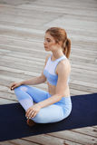 Young beautiful blonde girl practicing yoga outside. Royalty Free Stock Photos