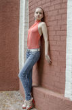 Young beautiful blonde girl in a red summer blouse and jeans posing flexible.  stock photography
