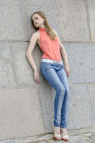 Young beautiful blonde girl in a red summer blouse and jeans posing flexible Stock Photography