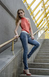 Young beautiful blonde girl in a red summer blouse and jeans posing flexible Royalty Free Stock Photography