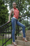Young beautiful blonde girl in a red summer blouse and jeans posing flexible Royalty Free Stock Image