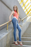 Young beautiful blonde girl in a red summer blouse and jeans posing flexible Royalty Free Stock Photo