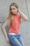 Young beautiful blonde girl in a red summer blouse and jeans posing flexible Stock Photos