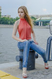 Young beautiful blonde girl in a red summer blouse and jeans posing flexible Stock Images