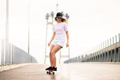 Young Beautiful Blonde Girl Riding Bright Skateboard on the Bridge. Young Beautiful Blonde Girl Riding Orange Skateboard on the Bridge stock image