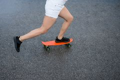 Young Beautiful Blonde Girl Riding Bright Skateboard on the Bridge Stock Photo