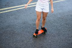 Young Beautiful Blonde Girl Riding Bright Skateboard on the Bridge Royalty Free Stock Photo