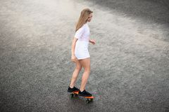 Young Beautiful Blonde Girl Riding Bright Skateboard on the Bridge. Young Beautiful Blonde Girl Riding Orange Skateboard on the Bridge royalty free stock photo