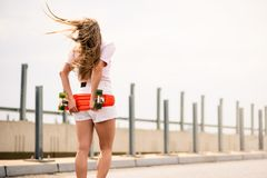 Young Beautiful Blonde Girl Riding Bright Skateboard on the Bridge. Young Beautiful Blonde Girl with Orange Skateboard on the Bridge royalty free stock photography