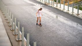 Young Beautiful Blonde Girl Riding Bright Skateboard on the Bridge Stock Photos