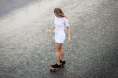 Young Beautiful Blonde Girl Riding Bright Skateboard on the Bridge. Young Beautiful Blonde Girl Riding Orange Skateboard on the Bridge royalty free stock images