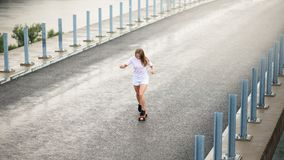 Young Beautiful Blonde Girl Riding Bright Skateboard on the Bridge Royalty Free Stock Photos