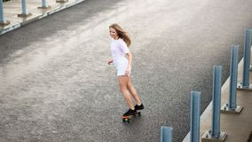 Young Beautiful Blonde Girl Riding Bright Skateboard on the Bridge Royalty Free Stock Images