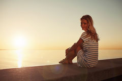 Young beautiful blonde girl sits on the beach and enjoy the sunr Royalty Free Stock Photo
