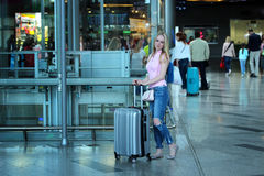 Young beautiful blonde girl standing close up with her silver suitcase in the airport.  Royalty Free Stock Image