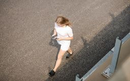 Young Beautiful Blonde Girl Using Smartphone while Walking on the Road stock photography