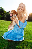 Young beautiful blonde girl walking, playing with beagle dog in park. Young beautiful blonde girl in blue dress smiling, walking, playing with beagle dog in royalty free stock photo