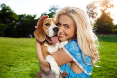 Young beautiful blonde girl walking, playing with beagle dog in park. Royalty Free Stock Photography