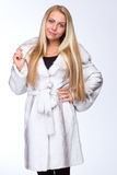 Young beautiful blonde girl in a white fur coat Royalty Free Stock Image
