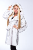 Young beautiful blonde girl in a white fur coat Stock Images