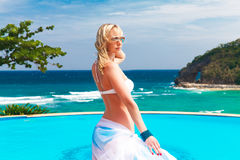 Young beautiful blonde girl in a white swimsuit with a waving pl Stock Photography