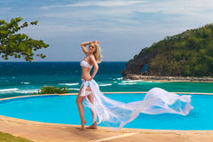 Young beautiful blonde girl in a white swimsuit with a waving pl Stock Images