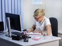 Young beautiful blonde girl is working in the office close-up.  Stock Image