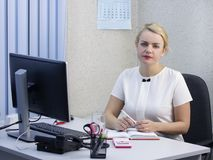 Young beautiful blonde girl is working in the office close-up. Young beautiful blonde girl is working in the office close-up Royalty Free Stock Photos