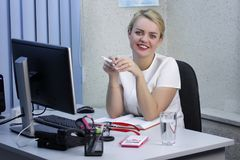 Young beautiful blonde girl is working in the office close-up Stock Images