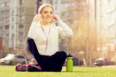 Young beautiful blonde hair fitness girl sitting on green stadium grass and listening music. Summer sport activity. Royalty Free Stock Photos