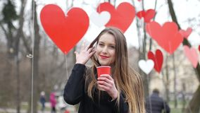 Young beautiful blonde hipster woman posing on the autumn park decorated with red paper hearts background with cup of. Takeaway coffee. Valentine's Day concept stock video