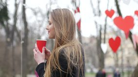 Young beautiful blonde hipster woman posing on the autumn park decorated with red paper hearts background with cup of. Takeaway coffee. Valentine's Day concept stock video footage