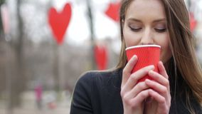 Young beautiful blonde hipster woman posing on the autumn park decorated with red paper hearts background drinking cup. Of takeaway coffee. Valentine's Day stock footage