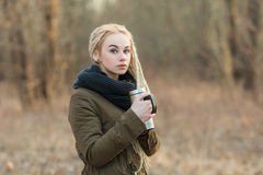 Young beautiful blonde hipster woman posing with thermos cup cold season outdoors Royalty Free Stock Image