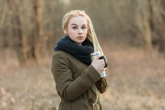 Young beautiful blonde hipster woman posing with thermos cup cold season outdoors Stock Photography