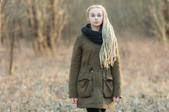 Young beautiful blonde hipster woman in scarf and parka with dreadlocks hairstyle cold season outdoors Stock Photography