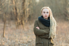 Young beautiful blonde hipster woman in scarf and parka posing with crossed hands cold season outdoors. Young beautiful blonde hipster woman in scarf and parka Royalty Free Stock Photo