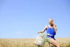 Young beautiful blonde lady on bicycle exposing. Portrait of young beautiful blonde lady in blue shirt and shorts sitting on bicycle exposing her face to sun in Stock Images