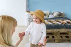 Young beautiful blonde mother and baby daughter in straw hat looking at each other and smiling Royalty Free Stock Photos