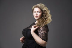 Young beautiful blonde plus size model in black dres, xxl woman portrait on gray studio background Royalty Free Stock Photos