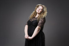 Young beautiful blonde plus size model in black dres, xxl woman portrait on gray studio background Stock Photography