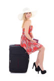 Young beautiful blonde in red dress sitting on suitcase isolated Royalty Free Stock Photos