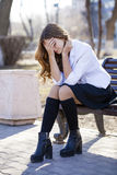 Young beautiful blonde schoolgirl sitting on a bench Royalty Free Stock Photo