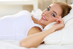 Young beautiful blonde smiling woman portrait wake up early morn. Ing after sleeping and lying in bed looking in camera. Sweet dreams and good morning, new day Stock Images